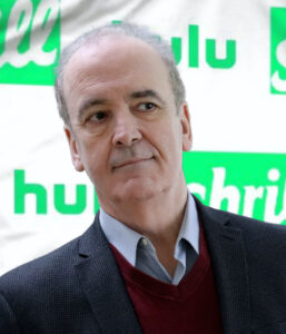 Actor Timothy Hill photographed in front of a step-and-repeat banner for the Hulu TV series Shrill.